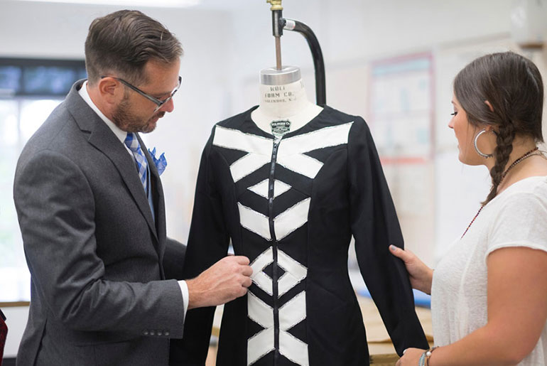 faculty member discusses fashion with female student