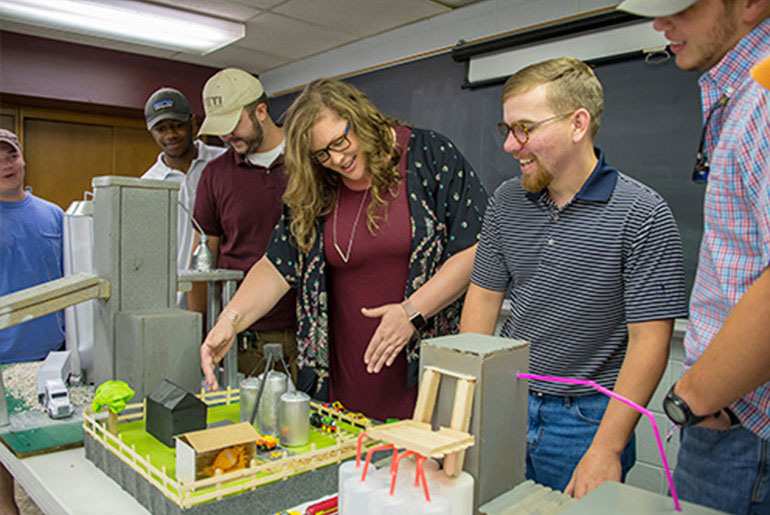 female professor looks at models developed by students