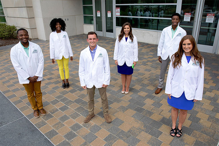 Six MSU students in white coats