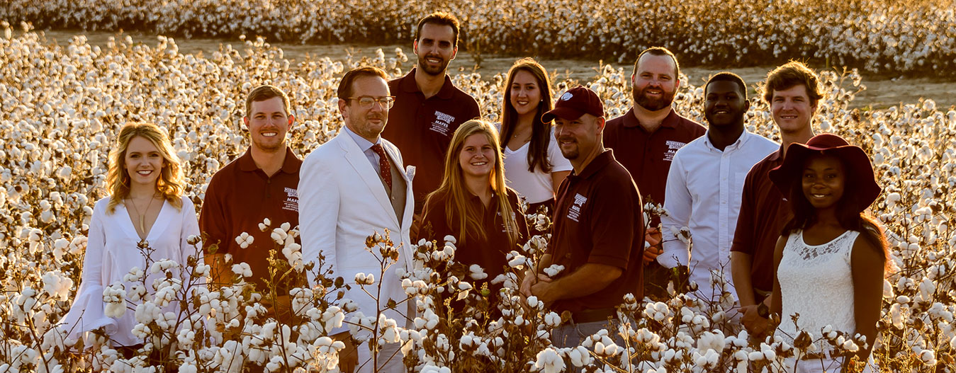 students and faculty in cotton field